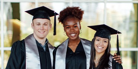 Three Graduates posing for a picture in Jostens graduation caps and gowns